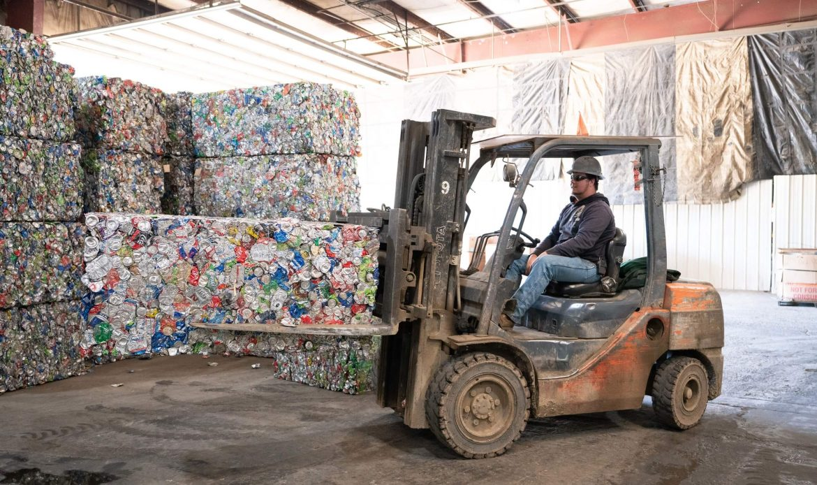 Recycled aluminum cans squashed into a brick and being moved by a fork lift in an east Tennessee scrap yard
